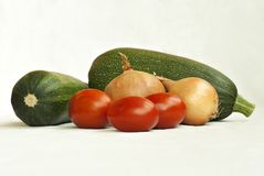 Courgettes, onions and tomatoes on a white background. Several vegetables zucchini, onion bulbs and tomatoes on a white background Stock Photos