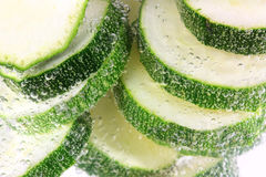 Courgettes sliced in water cooking Royalty Free Stock Image