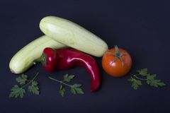 Courgettes with tomatoes and red pepper on black background. Composition from different vegetables on a dark background Royalty Free Stock Photos