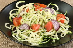 Courgetti. Spiralised corgette with red onion and tomato royalty free stock photography