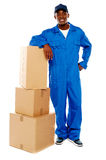 Courier boy standing beside boxes. Against white background, resting hand on them Stock Image