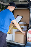 Courier and a car full of packages royalty free stock image