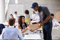 Courier Collecting Package From Businesswoman In Busy Office Stock Photography