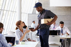 Courier Collecting Package From Businesswoman In Busy Office Royalty Free Stock Photography