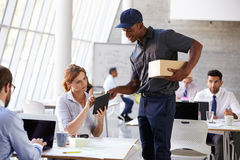 Courier Collecting Package From Businesswoman In Busy Office Stock Image