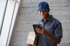 Courier Collecting Package From Office Stock Photo