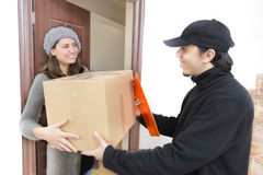 Courier Delivering a Package. To a happy woman stock photo