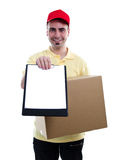 Courier delivering parcel. Delivery man in yellow polo and baseball hat with a parcel and a tablet isolated on white Royalty Free Stock Images