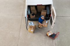 Courier delivering parcel. Delivery man holding cardboard box and unloading parcel for delivery. Top view of courier unloading parcels from van. High angle view royalty free stock images