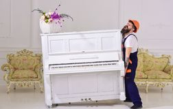 Courier delivers furniture, move out, relocation. Heavy loads concept. Man with beard worker in helmet and overalls. Lifts up, efforts to move piano, white stock photos