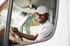 Courier Delivery. Black Man Driver Driving Delivery Car. With Boxes And Packages. High Resolution royalty free stock images