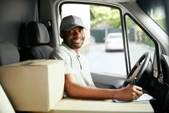 Courier Delivery. Black Man Driver Driving Delivery Car. With Boxes And Packages. High Resolution royalty free stock image