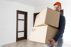 Courier delivery man with cardboard box in hands at home. Free shipping concept. Stock Photos