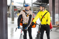 Courier Delivery Men With Bicycles Looking At Each Stock Images