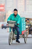Courier delivery service on his bike in winter time, Beijing, China. BEIJING-DEC. 4, 2012. Courier delivery service bike. Thanks to the country's e-commerce Stock Images