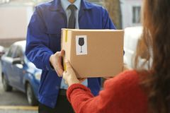 Courier giving parcel to customer,. Closeup Stock Photos