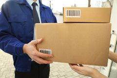 Courier giving parcels to customer. Closeup stock photography