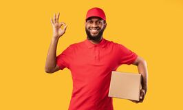 Free Courier Guy Holding Cardboard Box Gesturing Okay On Yellow Background Stock Images - 182652924