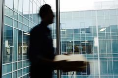 Courier haste. Blurry motion of delivery man walking along office building window while carrying pizza to one of clients Royalty Free Stock Photos