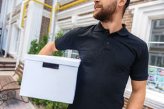 Courier holding a box in front of house stock photos