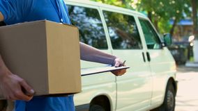 Courier holding cardboard box, checking clients form, express shipment service. Stock photo royalty free stock photos