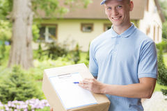 Courier holding a parcel and a clipboard stock image