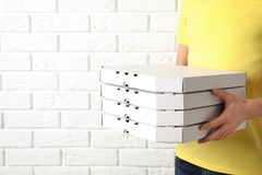 Courier holding pizza boxes near white brick wall, closeup with space for text. Food delivery service stock photo
