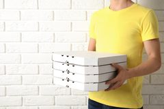 Courier holding pizza boxes near white brick wall, closeup with space for text. Food delivery service royalty free stock images