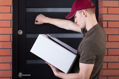 Courier knocking on customer's door Royalty Free Stock Image