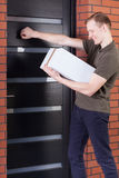 Courier knocking on doors stock photography