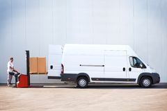 Package loading, the shipment has been processed in the parcel center. Courier is loading the van with parcels Royalty Free Stock Photography