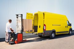 Package loading, the shipment has been processed in the parcel center. Courier is loading the van with parcels Stock Image