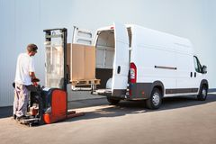 Package loading, the shipment has been processed in the parcel center. Courier is loading the van with parcels Stock Photos