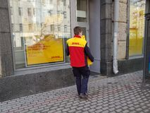 Courier of a logistics company DHL carries boxes Stock Photos