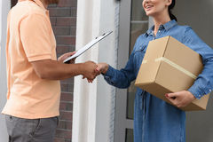 Courier making delivery to beautiful woman. Thank you for timely delivery. Cropped shot of beautiful young women holding cardboard box and smiling while shaking stock photo