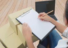 Courier making notes in delivery receipt among parcels on boxes royalty free stock photo