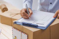 Courier making notes in delivery receipt among parcels at table stock photography
