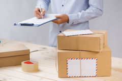 Courier making notes in delivery receipt among parcels at table stock photos