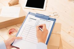 Courier making notes in delivery receipt among parcels at table royalty free stock photos