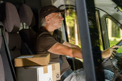 Courier man driving cargo car delivering package Stock Photography