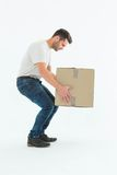 Courier man picking up cardboard box Stock Image