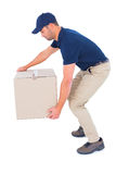 Courier man picking up cardboard box Royalty Free Stock Image