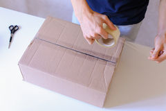 Courier Manstanding in Post Office, Glue Tape Brown Box on All S Stock Images