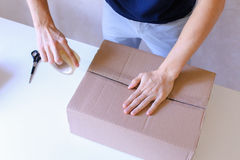 Courier Manstanding in Post Office, Glue Tape Brown Box on All S Royalty Free Stock Images
