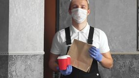 Courier in medical gloves protective surgical mask holding paper bag lunch, coffee cup enter the house door. safe delivery service