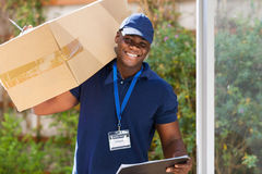 Courier with parcel. Cheerful african courier standing with parcel at the door royalty free stock photography