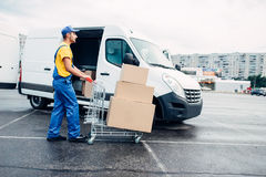 Courier with parcel trolley against logistic truck. Male courier with parcel trolley against truck with carton boxes. Distribution business. Cargo delivery Royalty Free Stock Image