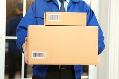 Courier with parcels on doorstep,. Closeup Stock Image