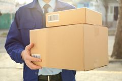 Courier with parcels outdoors,. Closeup Royalty Free Stock Image
