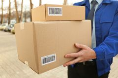 Courier with parcels outdoors,. Closeup Stock Photography